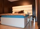 postel s čalouneným čelem a zdrcadlovými stolky